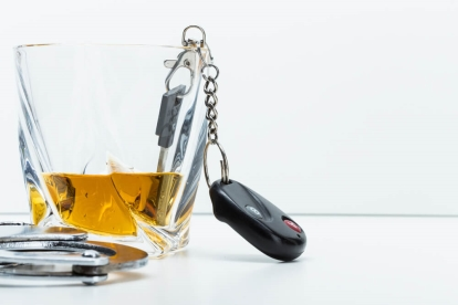 Glass of Alcohol with Keys and Cuffs Next to It